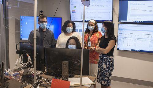Au Centre de commandement numérique de l'HGJ, les membres de l'équipe discutent du congé ou du transfert des patients.