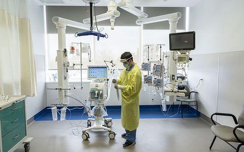 L'inhalothérapeute Brian Camacho vérifie son équipement dans la chambre d'un patient contaminé par la COVID-19, au pavillon K.